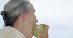 older woman eating fruit photo